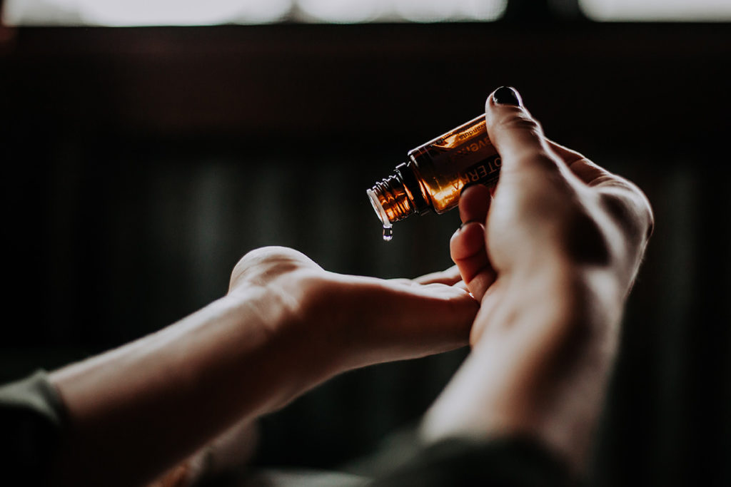Picture of a person putting a drop of essential oil into their hands.